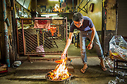 """09 FEBRUARY 2013 - BANGKOK, THAILAND:   A man burns """"hell money"""" in front of his home in Chinatown in Bangkok for Chinese New Year. It's a Chinese custom to burn fake money and other fake valuables in Chinese New Year and some other holidays because it is believed the money will by their ancestors in the afterlife. Bangkok has a large Chinese emigrant population, most of whom settled in Thailand in the 18th and 19th centuries. Chinese, or Lunar, New Year is celebrated with fireworks and parades in Chinese communities throughout Thailand. The coming year will be the """"Year of the Snake"""" in the Chinese zodiac.  PHOTO BY JACK KURTZ"""