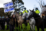 MELBOURNE, VIC - SEPTEMBER 05: A woman holding a placard yells at mounted police during the Anti-Lockdown Protest on September 05, 2020 in Sydney, Australia. Stage 4 restrictions are in place from 6pm on Sunday 2 August for metropolitan Melbourne. This includes a curfew from 8pm to 5am every evening. During this time people are only allowed to leave their house for work, and essential health, care or safety reasons. (Photo by Dave Hewison/Speed Media)