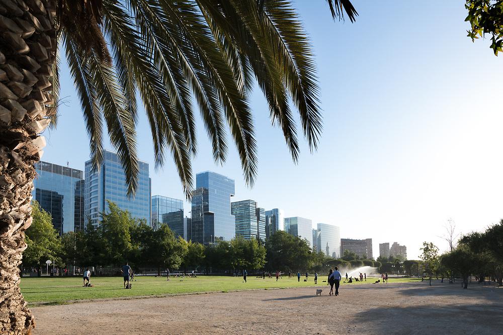 Santiago, Region Metropolitana, Chile - People enjoying at Parque Araucano, the main park in Las Condes district, surrounded by office buildings of Nueva Las Condes business center.