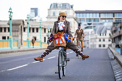 © Licensed to London News Pictures. 04/05/2019. London, UK. A woman lifts her feet from the peddles as she cycles across Southwark Bridge on the Tweed Run bike ride in Central London. The annual event sees hundreds of people cycle around the capital past various landmarks wearing vintage tweed outfits. Photo credit: Rob Pinney/LNP