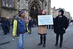© Licensed to London News Pictures.  03/11/2017; Bristol, UK. *NOTE: school children visible in the picture.* Campaigners from the group Countering Colston hold signs outside Bristol Cathedral during the commemoration service of Colston Girls School. The name of Edward Colston is a controversial issue in Bristol. Colston is associated with the slave trade but he also gave away a lot of his wealth to the city and the money helped found various organisations and several schools bear the name Colston. One of Bristol's main music venues, the Colston Hall, will change its name following a refurbishment. Colston Girls School have decided not to change the name of the school but have removed all references to Colston from the commemoration service. Picture credit : Simon Chapman/LNP