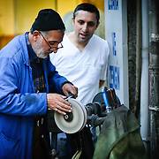A street vendor uses a mobile grinder to sharpen knives in downtown Istanbul, Turkey.