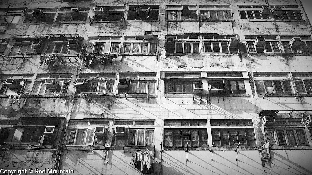 The scattered scene of hanging clothes and airconditioning units outside an old appartment building in Hong Kong