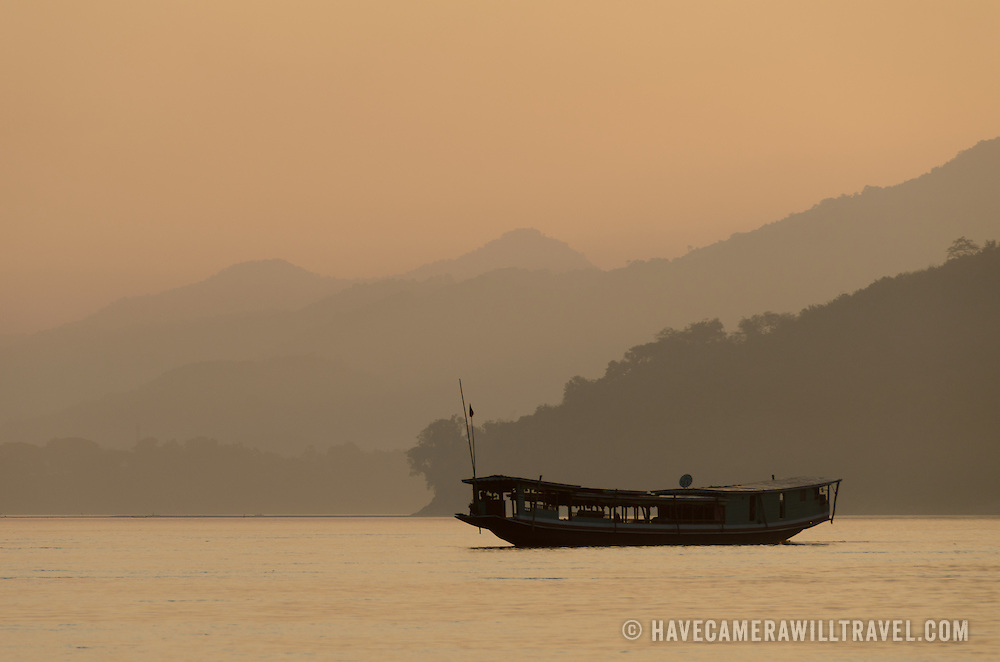 A boat sits in the middle of the river on a hazy sunset on the Mekong River near Luang Prabang, Laos.