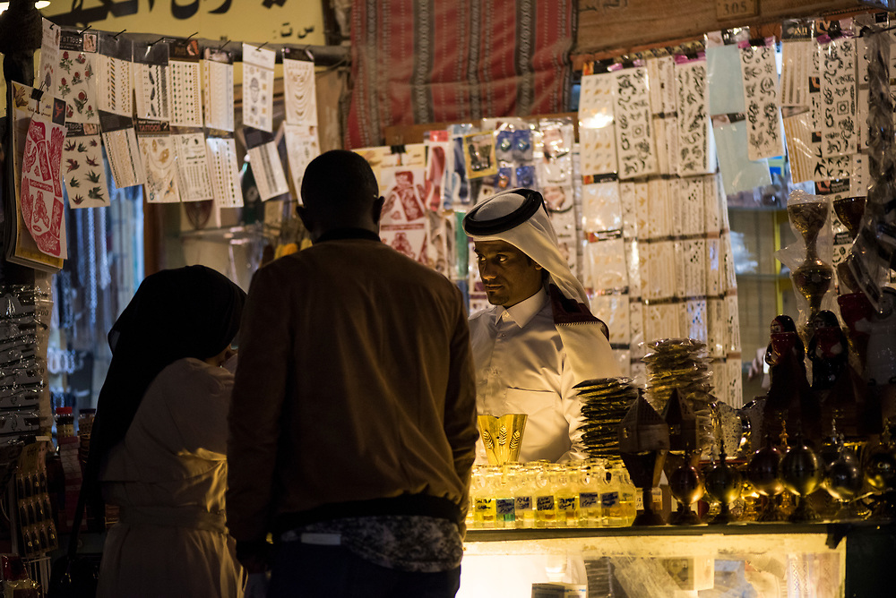 A shopkeeper interacts with customers at his shop at night in Souk Waqif in Doha, Qatar.