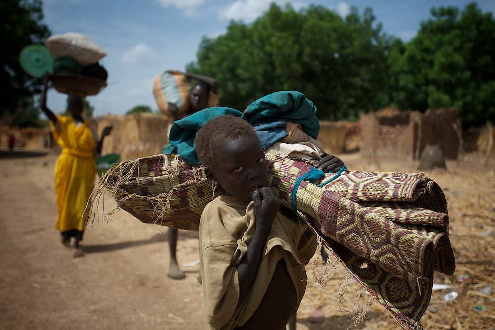 April 28, 2012 - Buram, Nuba Mountains, South Kordofan, Sudan: A Nuba family passes by Buram village during the first stretch of a three to four day journey to a refugee camp in the neighbor South Sudan. Thousands of people have in the past months fled the bombardments and hunger in South Kordofan...Since the 6th of June 2011, the Sudan's Army Forces (SAF) initiated, under direct orders from President Bashir, an attack campaign against civil areas throughout the South Kordofan's province. Hundreds have been killed and many more injured...Local residents, of Nuba origin, have since lived in fear and the majority moved from their homes to caves in the nearby mountains. Others chose to find refuge in South Sudan, driven by the lack of food cause by the agriculture production halt due to the constant bombardments of rural areas. (Paulo Nunes dos Santos/Polaris)