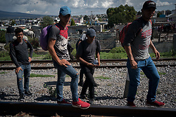 A group of migrant workers walk along railway tracks as they wait for a train heading north. Everyone in the group has worked in at least one trade, and they are hoping to find work in the US.