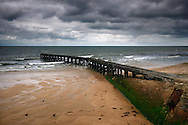 The old wooden pier at the beach of Grancamp-Maisy, a small village on the coast of Lower Normandy in France placed right in the middle of Utah and Omaha beach, two of the five beaches used by the Allies o the D-Day invasion. Taken on a overcast evening of mid August.