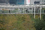 businesspeople walking on a bridge between office buildings