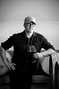A Black and white portrait of Todd Alexander winemaker for Force Majeure in the The Rocks District AVA holding a glass of wine in his production space