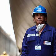 latino worker standing in ship yard