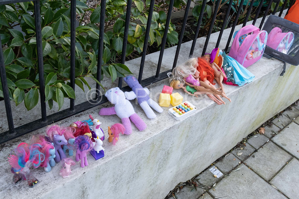 The discarded possessions of a young girl, part of a winters decluttering, consists of My Little Ponies and Barbie Dolls, which are lined-up on a wall outside a residential home in Herne Hill, south London, on 23rd January 2021, in London, England.