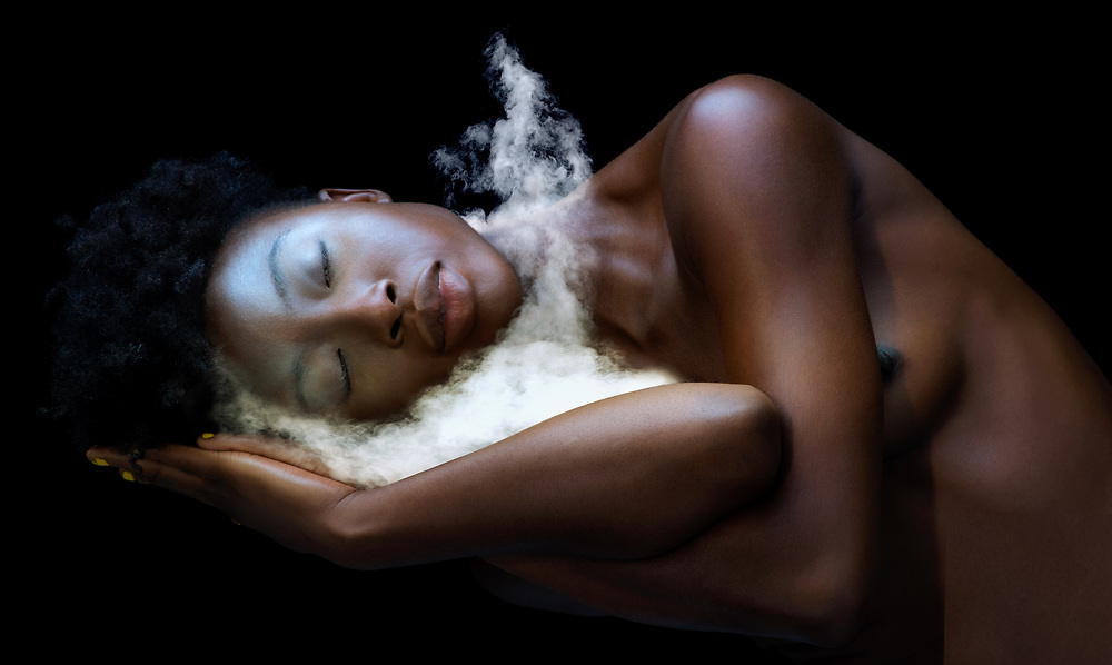 Black woman leaning into her arms as a small flow of fog drapes over her shoulder onto her arms and hands.  Her eyes are closed.