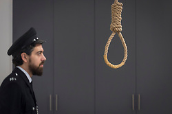 "© Licensed to London News Pictures. 13/11/2018. LONDON, UK. A staff member, posing as a prison guard, views a hangman's noose.  Preview of ""Glad I Did It"", a new work by Irish artist Christina Reihill at Bermondsey Project Space.  The interactive artwork looks at the life and death of Ruth Ellis, the last woman to be hanged in Britain, after she shot her lover, racing driver, David Blakely in 1955.  On display are the artist's interpretation of Ruth Ellis' prison cell, including furniture and props, the hanging room together with a video display of the artist in conversation.   The show runs 14 November to 1 December 2018.  Photo credit: Stephen Chung/LNP"