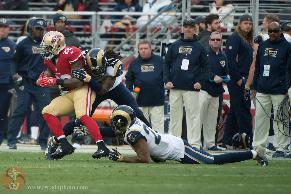 January 3, 2016; Santa Clara, CA, USA; San Francisco 49ers running back Mike Davis (22) is tackled by St. Louis Rams outside linebacker Mark Barron (26) and cornerback Trumaine Johnson (22) during the second quarter at Levi's Stadium. The 49ers defeated the Rams 19-16.