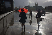 A woman carries a red umbrella crosses London Bridge in the rain, southwards from the City on the north bank of the river Thames, to Southwark on the southern side. Heavy rain has just fallen on the streets and pavements of London leaving them shiny and wet and with added strong sunshine, the coloured brolley stands out from an otherwise monochrome background. There has been a crossing over the Thames since the Roman era, with successive bridges from modern bridge (1971-), Victorian stone arch (1832-1968), Medieval stone arch (1176-1832) and various wooden bridges (AD50-1176).