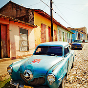 A pair of vintage cars parked on a colorful street in Trinidad, Cuba.<br />