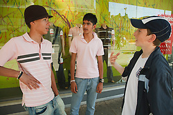 Group of teenage boys in town outside shop.