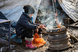 © Licensed to London News Pictures. 23/01/2016. Dunkirk, France. A young boy sits next to a fire in the migrant camp in Dunkirk, northern France where Leader of the Labour Party JEREMY CORBYN is due to visits today (Sat). Thousands of migrants and refugees at living in temporary accommodation as they attempt to reach the UK. Photo credit: Ben Cawthra/LNP