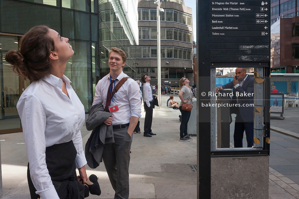 A missing panel in a street directions sign, frames a businessman on his phone, beneath the Monument where the Great Fire of London of 1666 is commemorated, in the City of London.