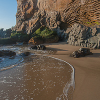 Colorful eroded sedimentary rocks rise above the waves at Panther Beach, north of Santa Cruz, California.