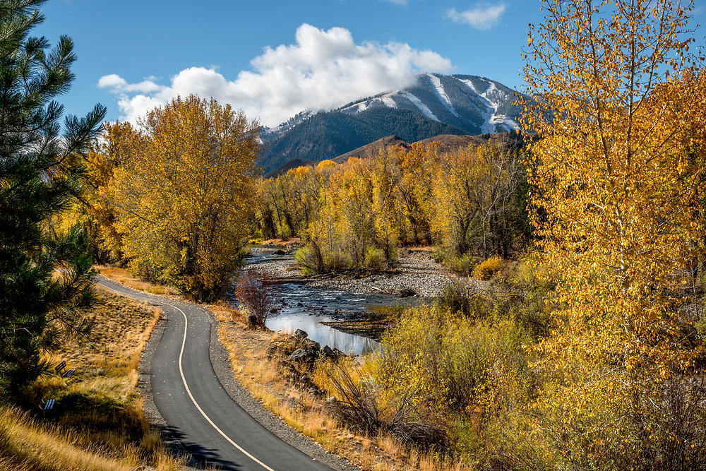Autumn colors get extra color saturation from recent rain with lifting clouds over Baldy Mountain with bike path along the Wood River in Sun Valley Idaho. Licensing and Open Edition Prints.