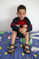 Young boy sitting on bed,