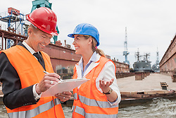 Dockers explaining to a manager during inspection of an industrial harbour, Hamburg, Germany