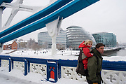 Heavy overnight snowfall covers London in a thick blanket of fine snow. The heaviest snowfall in decades. A father carries his daughter in a back pack across a snow covered Tower Bridge.
