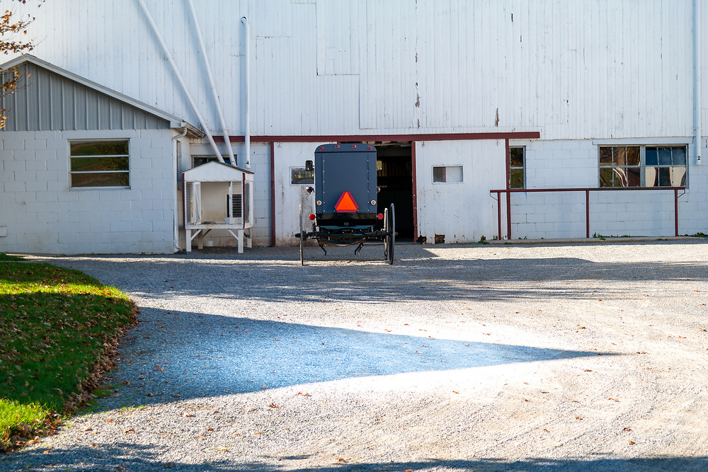 Gordonville, PA - October 6, 2014: A parked Amish buggy parked in the driveway near a white barn.