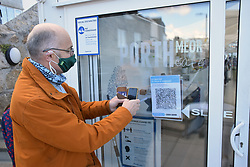 Man using the NHS Coronavirus track and trace app at Porthmeor beach cafe, St Ives, Cornwall, UK Oct 2020 MR