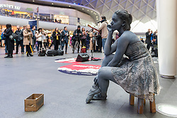 """© Licensed to London News Pictures. 16/03/2016. London, UK. Pippa Moss, known as the """"Lady of Stone"""" strikes a pose. Buskers and street performers entertain morning commuters in King's Cross station, as this year's Busk in London programme is launched.  Supported by the Mayor of London, the festival joins the International Busking Day and National Busking Day initiatives to celebrate street performances. Photo credit : Stephen Chung/LNP"""