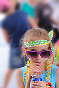 9 year old child dressed as a flower-child hippie drinking softdrink from a can.