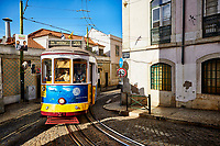 The sun sets on a trolley as it moves through the Alfama neighborhood of Lisbon, Portugal