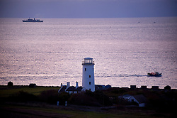 Boats passing the Old Lower Lighthouse at dawn, Isle of Portland, Dorset, England, UK.