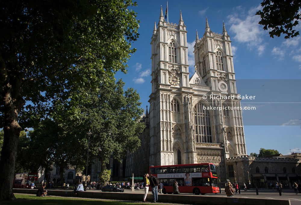 The tall western facade of London's Westminster Abbey with a red London double-decker bus passing-by.