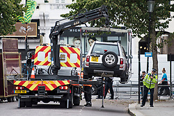 © Licensed to London News Pictures. 26/08/2018. London, UK. A vehicle parked on the carnival route being removed at family day of the 2018 Notting Hill Carnival. Up to 1 million people are expected to attend this weekend's event that is one of the worlds largest street festivals. Photo credit: Ben Cawthra/LNP