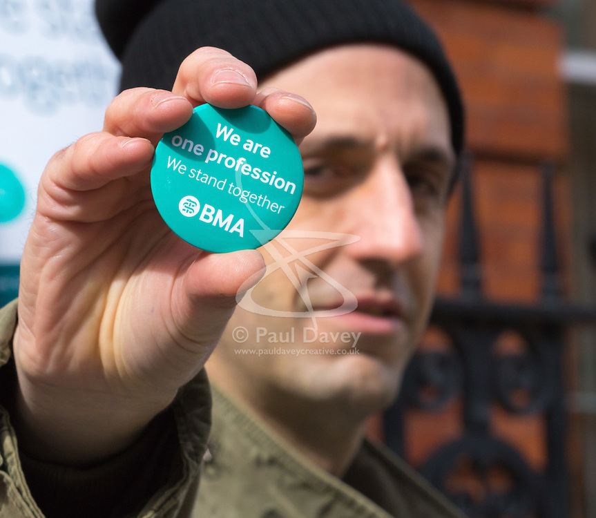 "Great Ormond Street Hospital, London, April 26th 2016. XA man holds up a ""We are one profession"" BMA badge as striking junior doctors picket outside Great Ormond Street Hospital for Children."