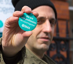 """Great Ormond Street Hospital, London, April 26th 2016. XA man holds up a """"We are one profession"""" BMA badge as striking junior doctors picket outside Great Ormond Street Hospital for Children."""