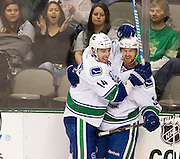 Henrik Sedin (33) of the Vancouver Canucks celebrates after scoring a goal with teammate Alexandre Burrows (14) while fans react in the background on Thursday, February 21, 2013 at the American Airlines Center in Dallas, Texas. (Cooper Neill/The Dallas Morning News)