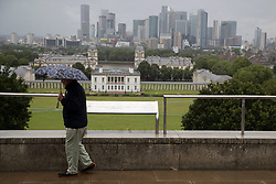 © Licensed to London News Pictures. 08/08/2021. London, UK. A man uses an umbrella to shelter from rain in Greenwich Park in South East London. A yellow weather warning for thunderstorms is in place for parts of England. Photo credit: George Cracknell Wright/LNP
