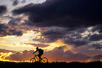 A dramatic sky silhouettes a mountain biker in Jackson Hole, Wyoming.
