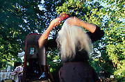 Edna brushes her hair in the early morning. Romany gypsies, Leslie and Edna traveling with a traditional bowtop wagon in the English countryside...English Romany Gypsies traditionally traveled the country roads camping nearby towns and villages, choosing the grassy roadside banks, where they tethered their horses, or in farmer's fields, when they were allowed. Travelling in bowtop wagons drawn by horses, and before that with tents, sometimes with horse drawn carts or just by foot. Often they worked as casual agricultural labourers, doing the seasons work. They also could earn their living in different ways, sometimes selling their wares, brass, tin, wood and cloth, such as embroidered cloths or lace, telling fortunes, music and dancing, and through crafts skills in basket making, plaiting chair bases, sharpening knives,  They would make fires from old wood, cleaning up after them when they moved on. There were several horse fairs, notably Appleby in Cumbria and Stow-on-Wold in the Cotswolds where they trade and sell horses, some traditions which keep to this day.