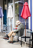 A bearded man reads at a French cafe in downtown Monterey, California on a quiet overcast morning