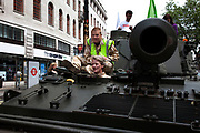 DRiver and navigator on the tank as it passes along The Strand. Campaigners and supporters from Oxfam and Amnesty International, as part of the Control Arms coalition, drive an Abbot gun tank around central London to highlight the need for a global Arms Trade Treaty (ATT) to be agreed during a United Nations conference next month (July 2012). London, England, UK. 27th June 2012.
