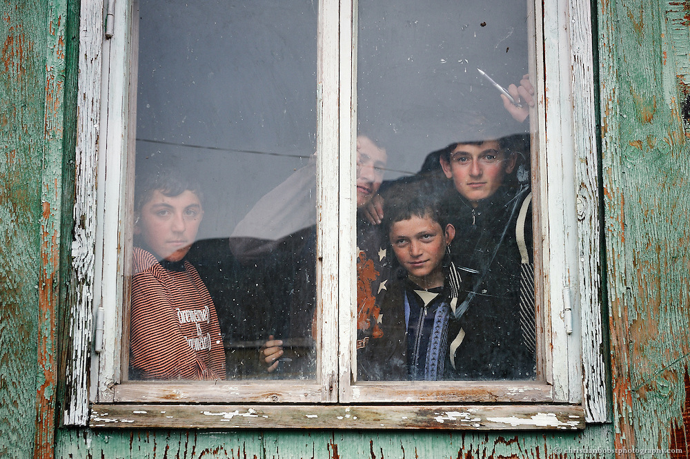 Portrait of 4 boys who glipsing out of the window of a schoolhouse in Mirashkhani, Georgia. Photographed for HEKS, a Swiss NGO.