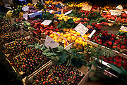 Lemons, cherries, and other fresh fruits fill up a stand at an outdoor market in Ponza, Italy