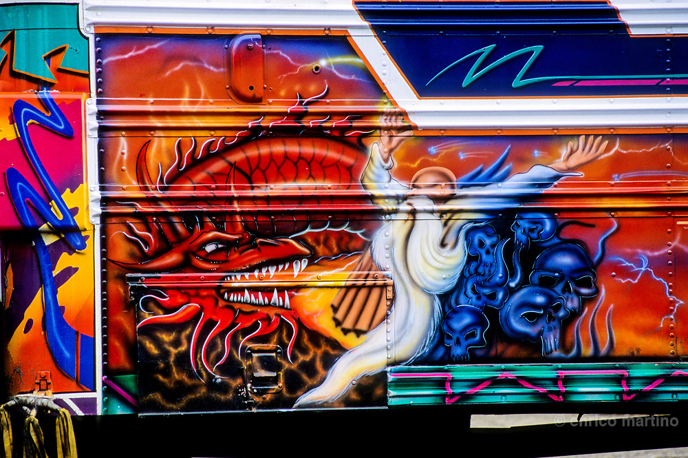 Creatively painted bus Diablos Rojos, Red Devils. Designs includes favorite saint, movie-star, cartoon character, driver's girlfriend name. The government projects new and more confortable bus, but a lot of people defends traditionals, and cheapers, old bus. One of most unique aspects of Panamà City, a true cultural experience, is a fleet of buses traditionally called diablos rojos, red devils, school buses creatively transformed into works of art by their owners in a folkloric style. Many buses have paintings of religious icons, pop culture heroes, actresses, sport stars, politicians. The drivers choose their own routes and on the front of the bus is usually painted the destination. Music at high volume, poor ventilation and lack of security transform the buses in a uncomfortable transport system. In 2003 the red devils (two percent of all vehicles) caused 14 percent of traffic accidents. Panamà's governement is trying the put end to the legend of Diablos Rojos but Panamà expresses its popular culture through the bus painting, in the way murals do for other cities, so this expression of popular art could end in few years.