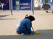 Ältere Frau bettelt vor einer Werbung für Mobiltelefone auf einer Straße im Zentrum der russischen Hauptstadt Moskau. <br /> <br /> Old woman is begging infront of an advertising for mobil phones on a street in the center of the Russian capitol Moscow.