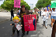 Amemeber of the Brown Berets carries an deffigy of Donald Trump and a reworked Time magazine cover during the Familes Belong Together rally in downtown Dallas. <br />The Brown Berets (Los Boinas Cafes) are a pro-Chicano organization that emerged during the Chicano Movement in the late 1960s founded by David Sanchez and remains active to the present day. -Wikipedia
